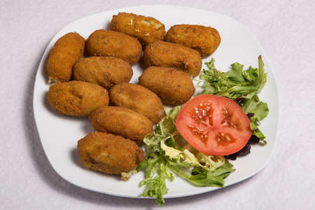 Potato croquettes (croquetas) with salad. Fast Food.