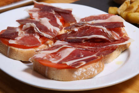 Delicious bread toast with natural tomato, extra virgin olive oil, Iberian ham