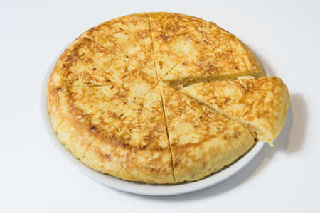 Piece of Omelet with eggs and potatoes on white plate. Spanish Omelette - Traditional tortilla tapas de patatas