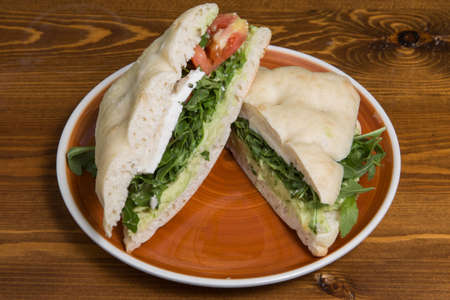 Ciabatta baguette sandwiches with avocado, cheese, rucula and tomato.