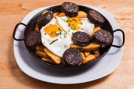 Tipical Spanish plate with potatoes, eggs with pepper and blood sausage, delicious with bread and a good wine