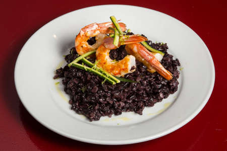 Arroz negro. Black rice. Typical spanish food in mediterranean zone made with rice, onion, tomato, squids and squid ink. Can be eated with ali oli sauce