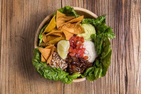 Bowl with nachos, vegetables, quinoa and cheese. Vegan food 版權商用圖片