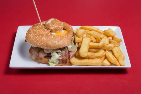 Burger with meat, egg, onion rings fries and potato wedges on wa white plate Stock Photo