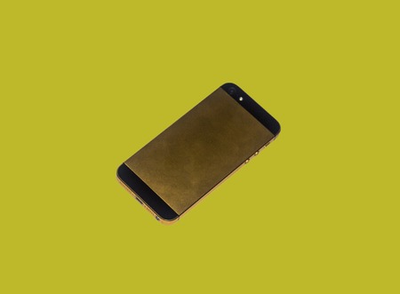 laconic: The isolated iPhone 5 gold on a yellow background Editorial