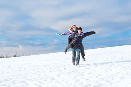 Young guy and the girl walk together in the winter photo