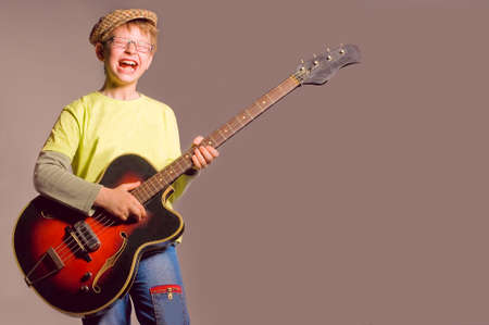 The young boy emotionally plays on a guitar  photo