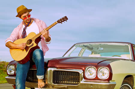 The young guy plays on a guitar sitting on a cowl of the old car Stock Photo - 7877090