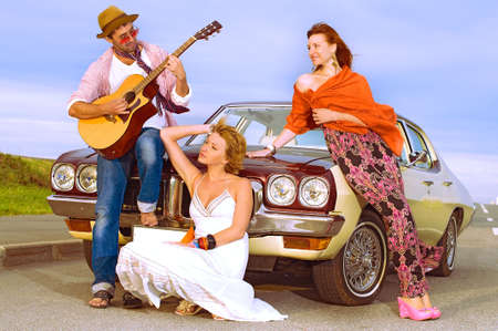 The young guy plays to two girls on a guitar sitting on a cowl of the car photo