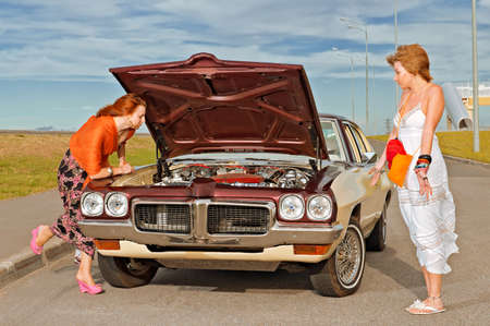 Two young girls  at the curb trying to understand - why the old American car broke down  photo