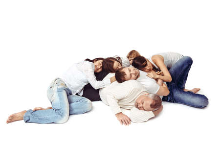 snoozing: People lie a heap on the floor and sleep. Family asleep on a white background in jeans and a light jacket. Stock Photo