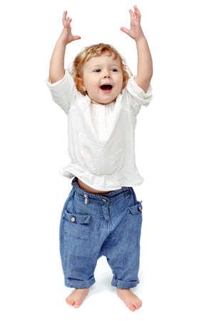 Il bambino balla su uno sfondo bianco, concedersi, corre, gioca, mani in alto