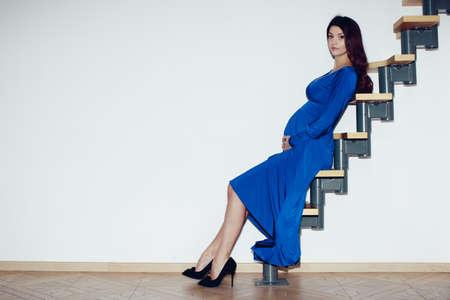 femme noire nue: Belle fille enceinte, brune, gros seins, les mains sur le ventre, robe bleue, assis sur une échelle contre un mur blanc dans le inter