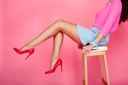 red heels: Beautiful female legs with red heels on pink background. Girl in short blue skirt sitting on a bar stool Stock Photo