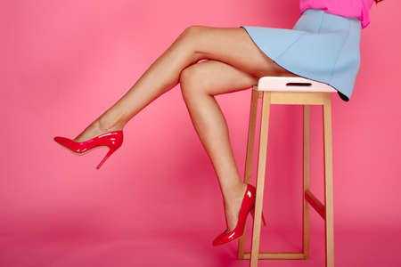 Beautiful female legs with red heels on pink background. Girl in short blue skirt sitting on a bar stool Banque d'images