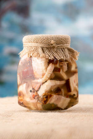 Canned fat meat, bacon in a glass jar close-up sacking and blue background