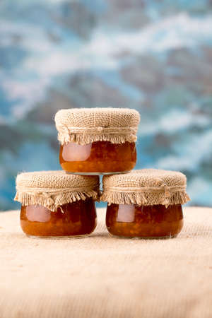 chicout�: Three cloudberry jam jars sacking and blue background Banque d'images