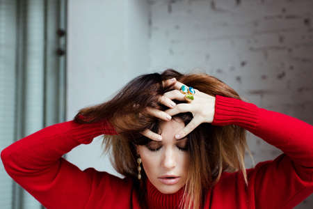 frantic: Beautiful girl in a red sweater and rings is holding her hands behind her head, frantic, bewildered, not understanding in white interior, Indoor