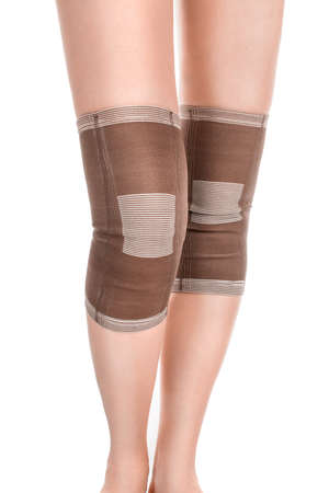 kneecap: Closeup of woman legs with two compression knee braces isolated on white