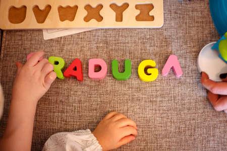 child education: Child hands writing word RADUGA on the tissue