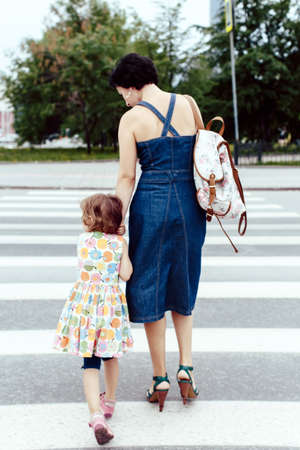 cross street with care: Daughter with her mother crossing the road at a pedestrian crossing, summer, park, road sign