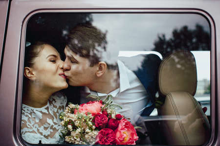 frowns: The groom kisses the bride, the view through the glass of the car