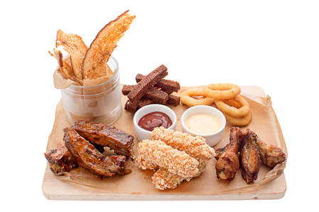 shrimp boat: On a wooden board beer snacks and sauces in a gravy boat. Cheese in batter, chicken wings, legs, onion, squid rings, bread, toast, chips, ketchup, sour cream, served beautifully