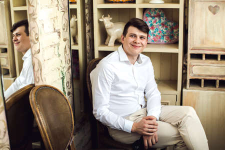 jazzbow: Emotive portrait of smiling handsome crazy hipster in white shirt sitting on a vintage chair with a smartphone in retro style interior Indoor shot Stock Photo