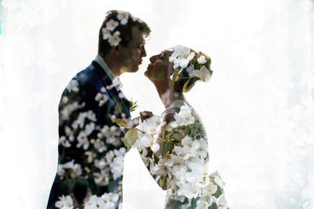 multiple exposure: Happy newlyweds kissing. Brunette bride  and  groom stand  silhouettes of happy double exposure, multiple exposure apple blossoms
