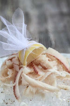 frozen fish: Stroganina- sliced raw frozen fish with  ice, wooden background.