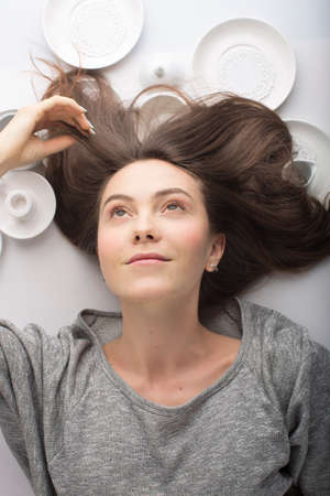 lies down: Brunette women lies on her back on a white background in dish: smiling, earring, happiness, flowing hair