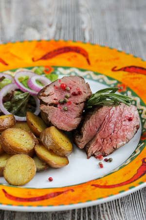 side of beef: Good-looking dish with beef, young baked potatoes and some fresh salad  on a side