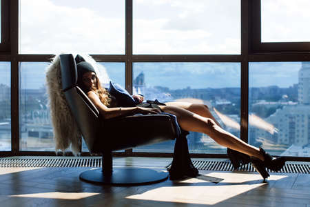 the thrown: Beautiful girl sitting on a chair her feet up on the window frame in a lace bodysuit, a blue coat and wearing shoes with heels can be seen outside the city. On a chair thrown over the white skin
