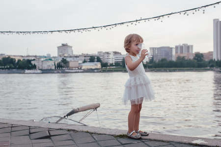 fullbody: Littel girl drinking a glass of water standing on the beach against the backdrop of the city, outdoor full-body Stock Photo
