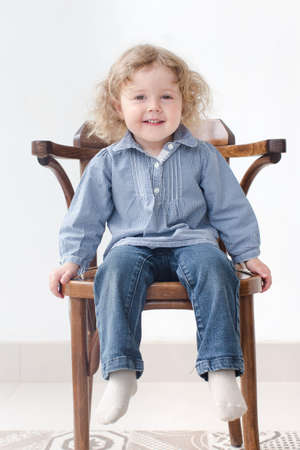 kinky: a small child with brown eyes sits on a wooden chair indoors on white background , smiling, looking directly at the camera, open and direct view, he wears  blue long sleeve shirt and jeans Stock Photo