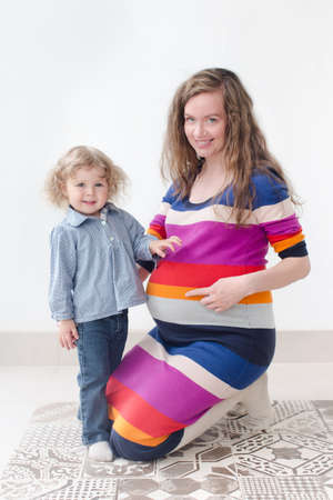 kinky: kinky mom and daughter sit side by side and touching pregnant belly, smiling, looking at the camera Stock Photo