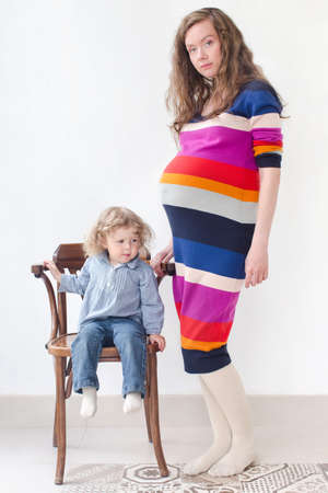30 years old: A pregnant woman 30 years old expecting second child standing together with her  little 2 year old kid sitting on a chair in the studio on a white background, looking at the camera