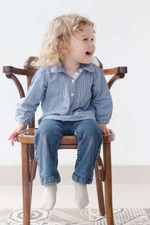 long sleeve shirt: little curly-haired girl sitting on a chair and laughs, looking in the direction, wears  blue long sleeve shirt and jeans