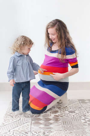 eldest: Pregnant woman in colorful dress in Studio is squatting and pointing to her eldest child on her belly , her daughter says something, answered,  asked about a baby who should be born Stock Photo