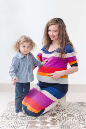 kinky: kinky young Pregnant woman in colorful clothing tells her elder child that baby will be born soon, pointing to her  belly, both looking at the camera and smile
