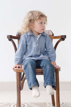 long sleeve shirt: A small child sits on a wooden chair in the Studio interior and looking around, something thought,  worry, he wears  blue long sleeve shirt and jeans
