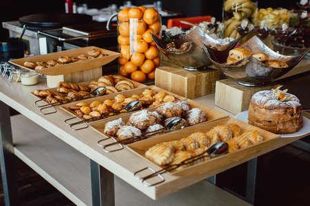 뷔페 테이블에 신선한 생 과자 및 만다린 구색