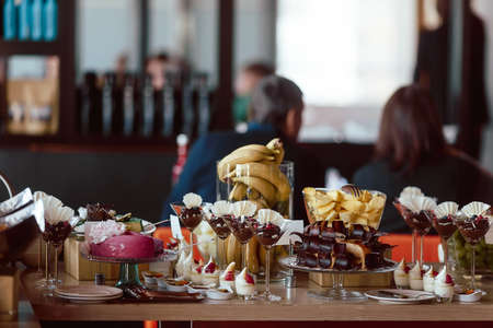 degradation: Assortment of different sweets: chocolate, mousse, fruit, cake, bananas, on holiday, on the background of people degradation restaurant, hotel Stock Photo