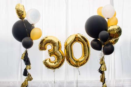 Decorazione per il compleanno, anniversario, celebrazione del trentesimo anniversario, sfondo bianco, oro e palloncini neri con nappe Archivio Fotografico