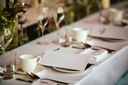paper plates: Table setting at wedding. Steampunk style. Glasses. plates, cutlery on craft paper with candlelights on background.