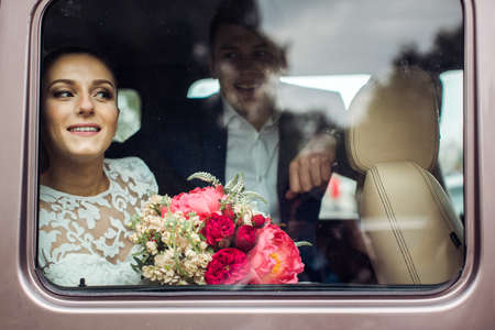 frowns: Bride and groom looking SUV through the car window into the future, the view through the glass of the car