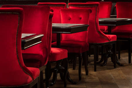 swanky: Red velvet chairs and tables on a wooden floor black, elegant piece of interior of restaurant Stock Photo