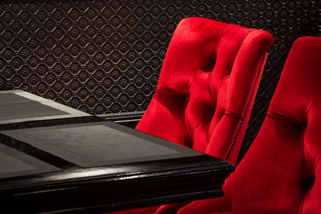 swanky: Red velvet chairs and table black, elegant piece of interior of restaurant