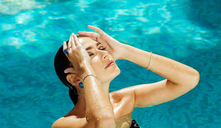swanky: Beautiful woman in the pool comes up in black swimsuit and jewelry. Girl brunette with closed eyes swimming in the ocean, sea