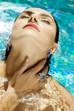 swanky: A woman with her eyes closed enjoying a swim in the water, close-up of face. Woman relaxing in a luxurious pool setting.